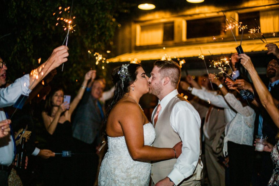 Bride and groom kissing during sparkler exit at the end of their Port Farms wedding