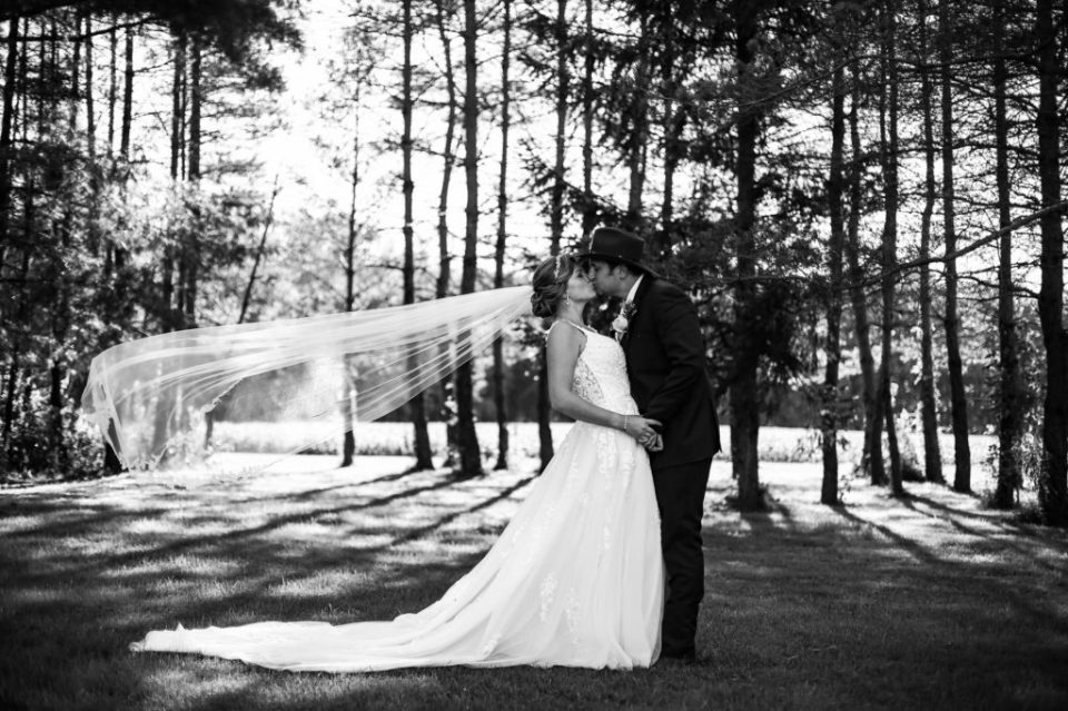 Bride and groom kissing with veil blowing in the wind on a family farm in Waterford PA