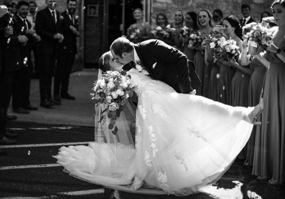 Bride and groom kissing during bubble exit at St George Church wedding