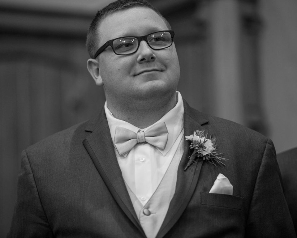 Groom smiling as he watches bride walk down the aisle in Erie, PA wedding