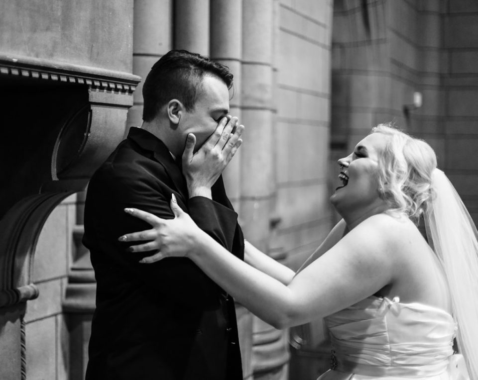 Groom covers his face in joyful surprise as he sees bride during first look photos at the Cathedral of Learning in Pittsburgh, PA