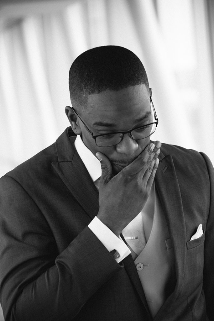 Groom rubs his chin as he reacts to seeing his bride during first look at the Sheraton Erie Bayfront Hotel