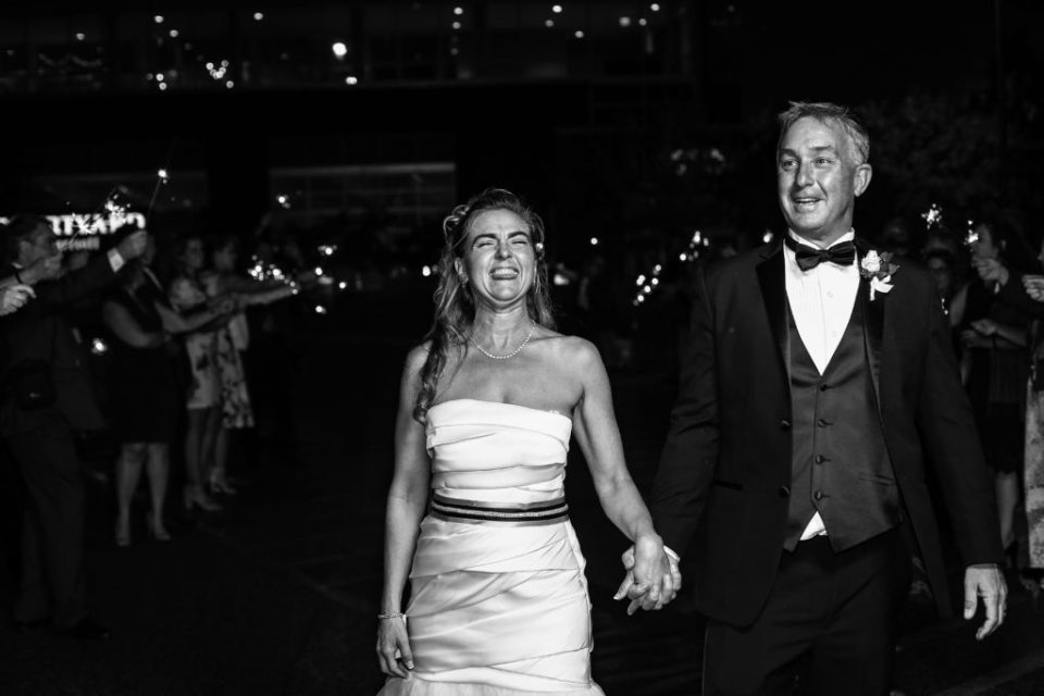 Couple laughing during the sparkler exit at Anchor Plaza wedding in Erie, PA