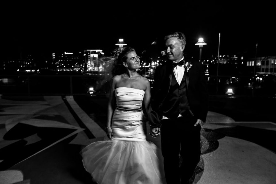 Bride and groom walking hand in hand on the platform of the BIcentennial Tower at night