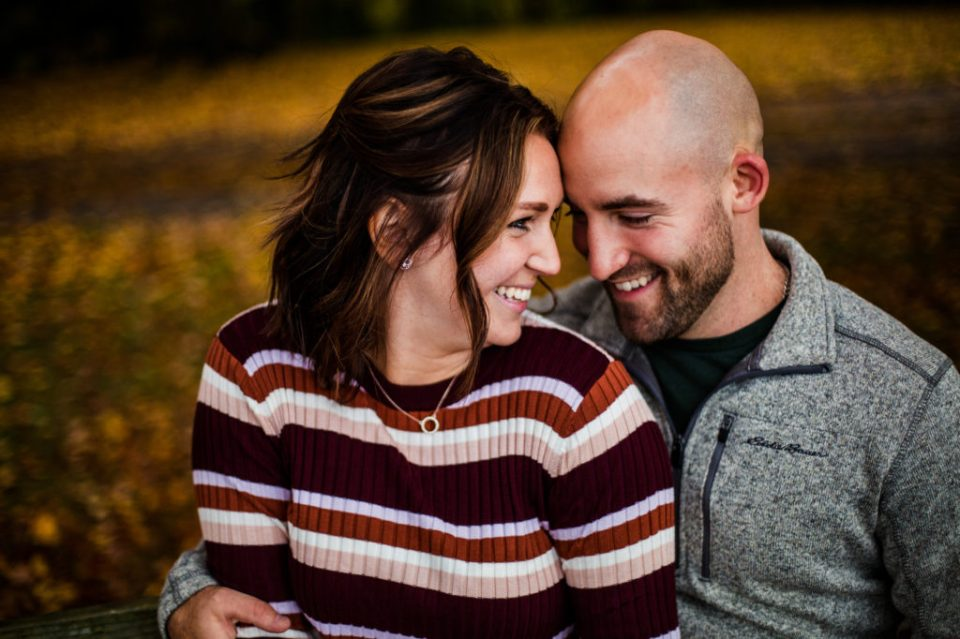 Engaged man and woman smiling at each other during Lake Erie Community Park engagement photos