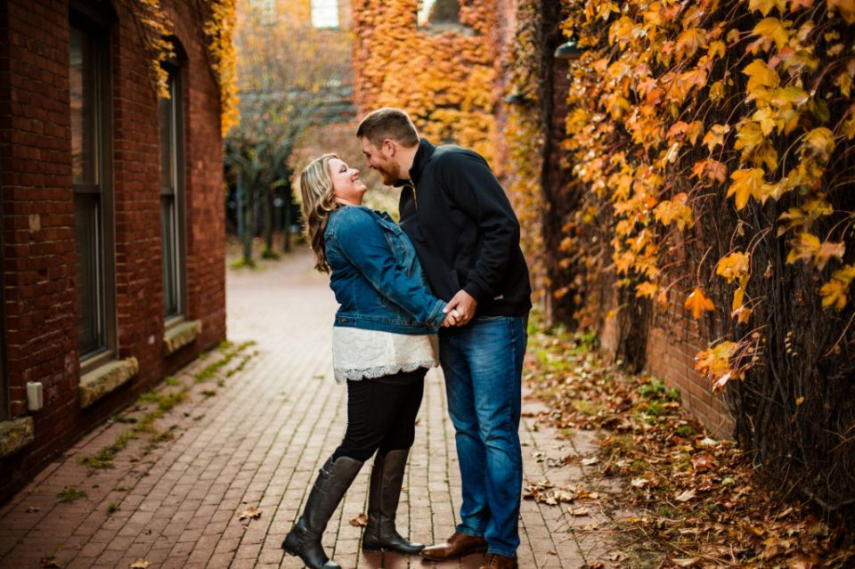 Couple laughing together as man leans in to kiss woman during Modern Tool Square engagement photos