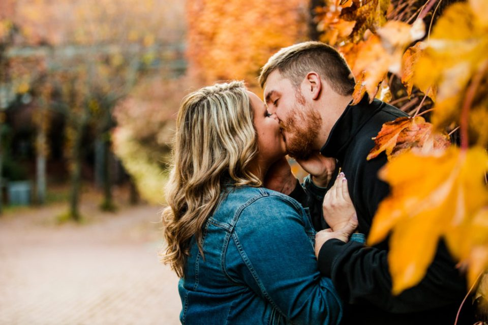 Woman kisses her fiance next to brick wall covered with yellow leaves for Modern Tool Square engagement photos