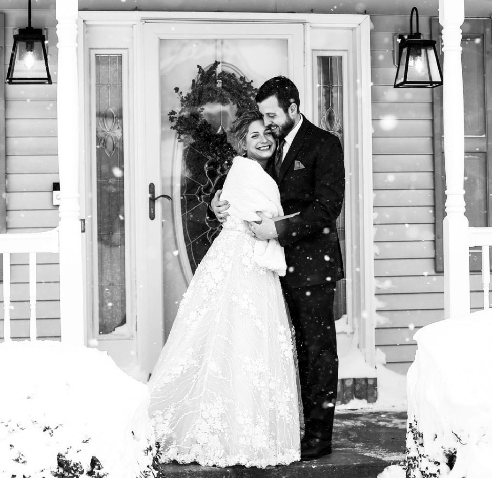 Bride and groom pose outside their home for their winter wedding in Erie PA