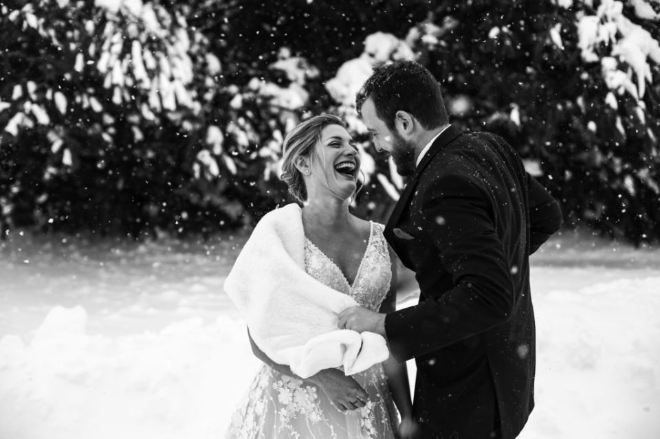 Bride and groom laughing as snow falls in Erie PA