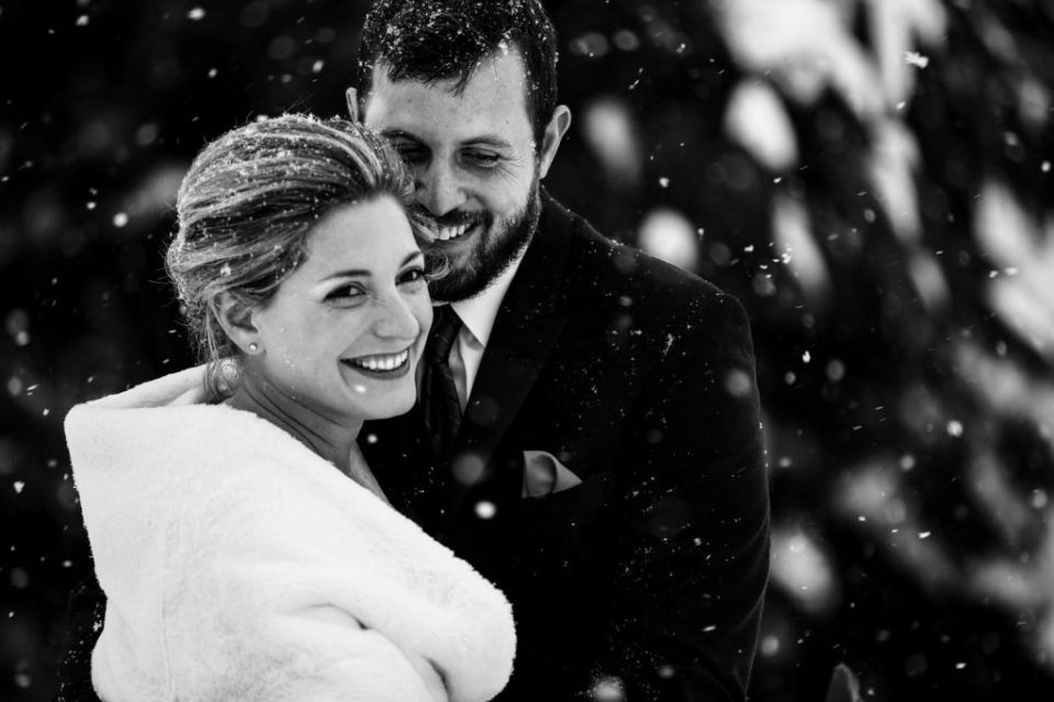 Smiling bride and groom surrounded by falling snow in Erie, PA