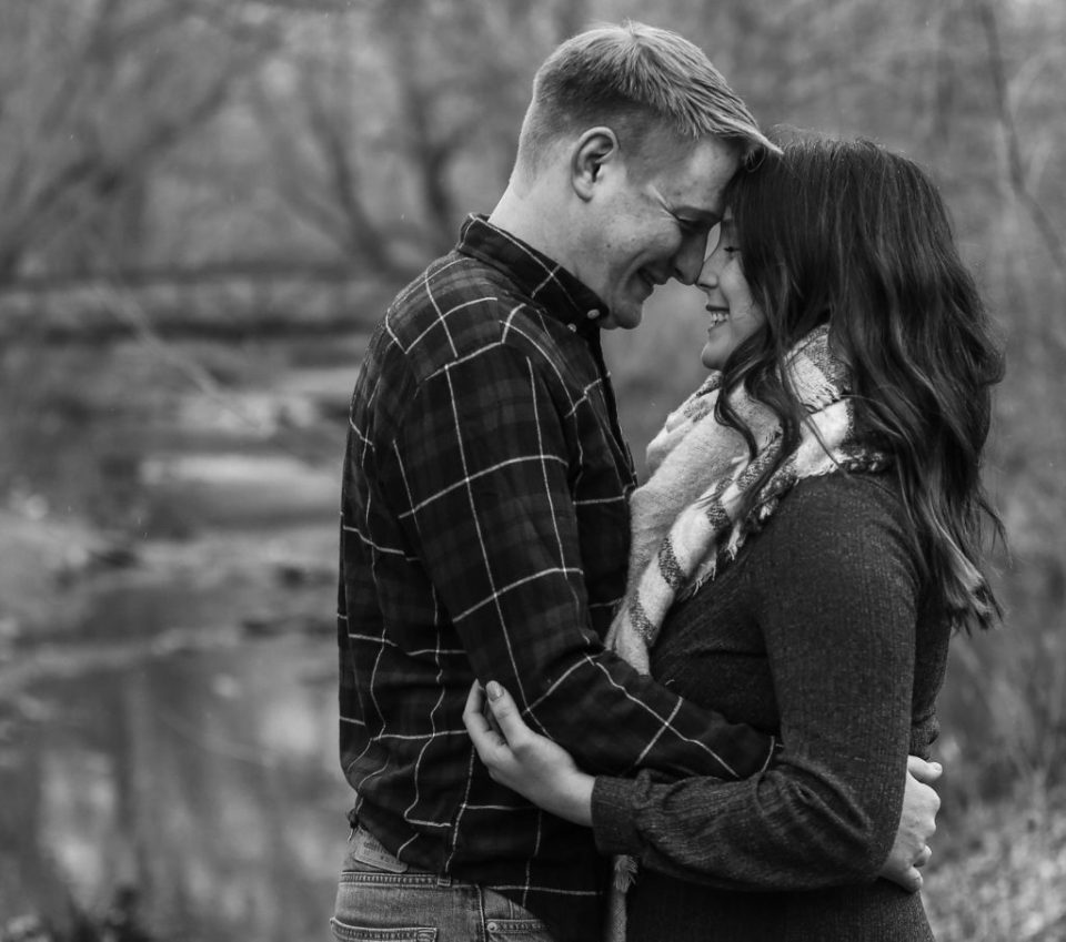 Couple touching foreheads and smiling in the woods at Erie, PA's Frontier Park