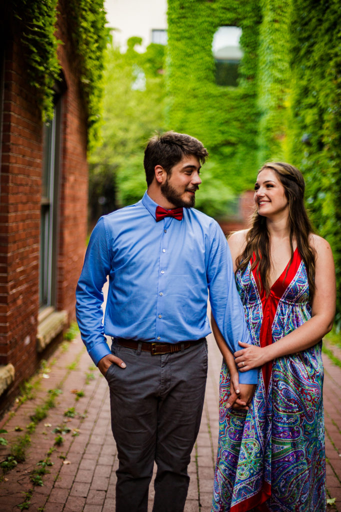 Couple holding hands while walking through Modern Tool Square for their engagement photos in Erie PA