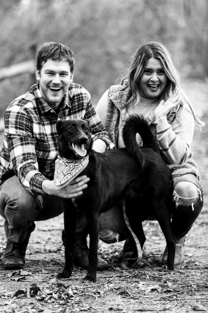 Laughing couple pose with their dog during their Frontier Park engagement photos in Erie PA