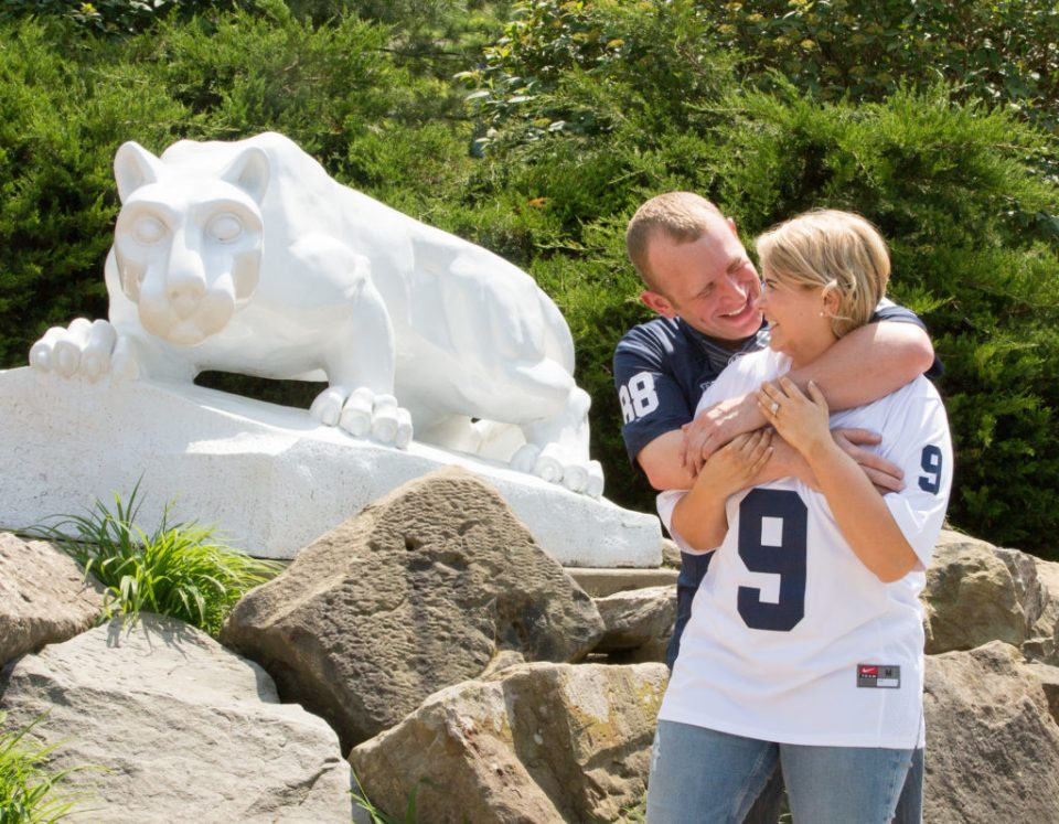 Man hugs finacee next to Nittany Lion on Penn State Behrend campus in Erie PA