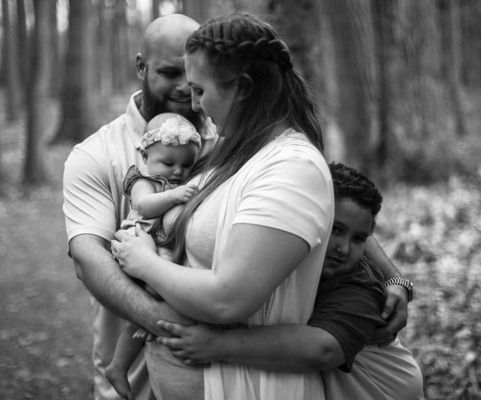 Father and son hug mother while she holds baby during Asbury Woods photo session