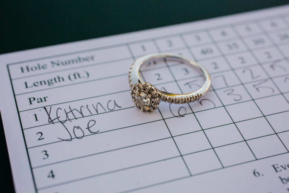 Engagement ring placed on mini golf score card from couple's first date