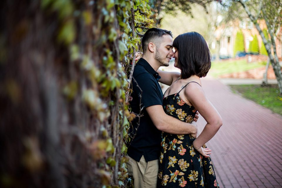 Couple about to kiss next to ivy covered brick wall for engagement photos in Modern Tool Square in Erie PA