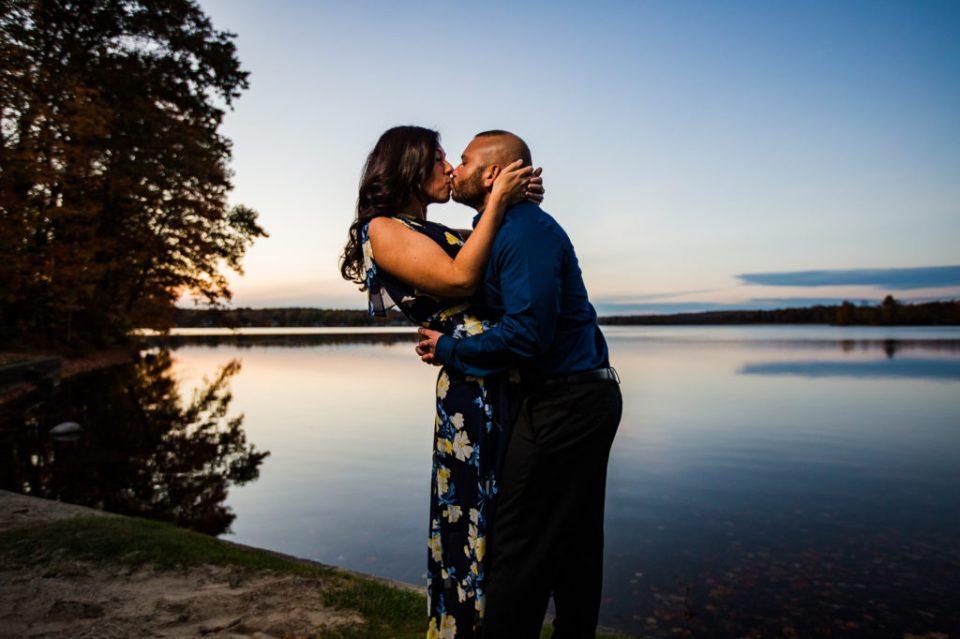 Engaged couple kissing next to Edinboro Lake at sunset