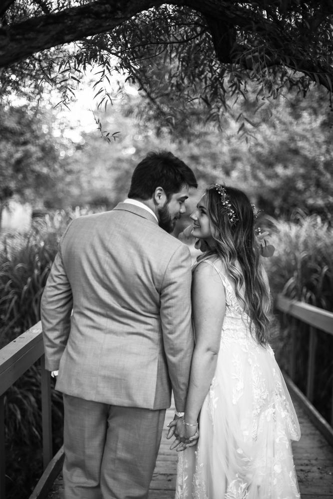 Smiling couple walk across bridge at Whispering Trees Manor wedding