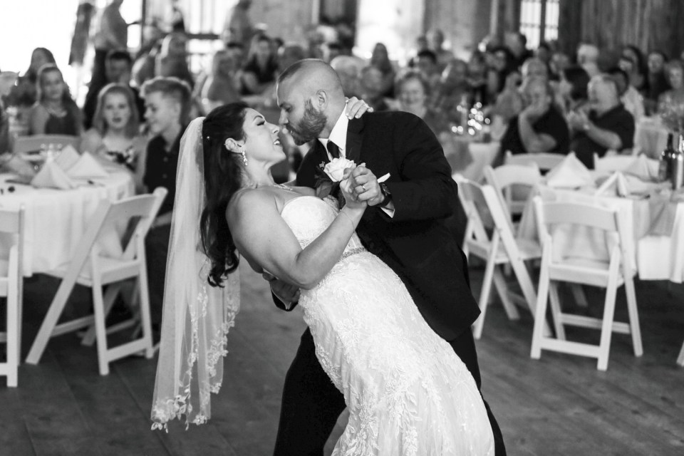 Groom dips bride during first dance at Port farms wedding reception