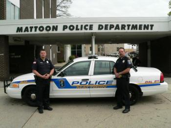 Two police officers standing in front of a police vehicle