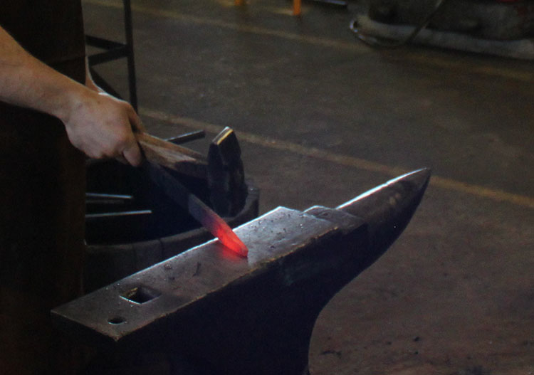 Strike while the iron's hot! Paul Nyborg, blacksmith, pounding out steel on his anvil.