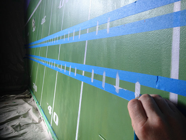 Carefully painting in the hash marks, with masking tape as a straight line to keep the edges sharp.