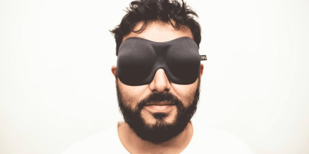 Man wearing a sleep mask with white shirt and white background