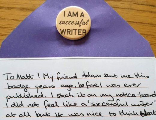 "The image shows a yellow badge reading ""I am a successful writer"" and a letter, which reads: ""To Matt! My friend Adam sent me this badge years ago, before I was ever published. I stuck it on my notice-board. I did not feel like a 'successful writer' at all but it was nice to think that at least one person did! It also made me think about what it meant to be 'successful' at all. So now I pass it on to you! Best writing wishes! Shirley x"""