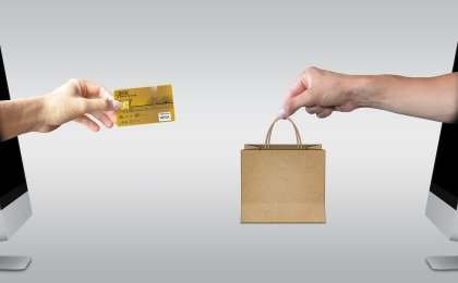 hand with credit card coming out of one computer screen to exchange with another hand coming out of the opposite computer screen with a shopping bag in its hand