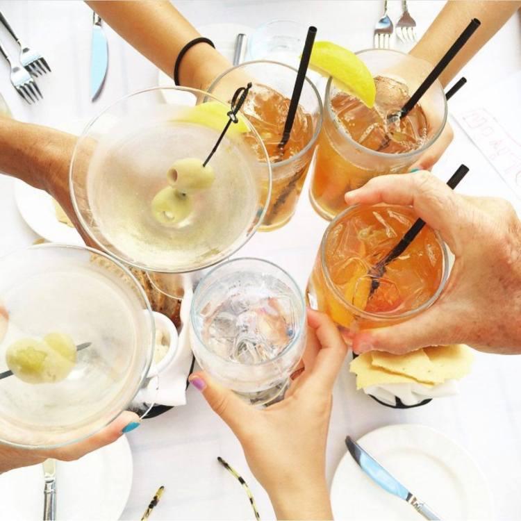 happy hour cocktails at nicks fish market maui - cheers toast salud