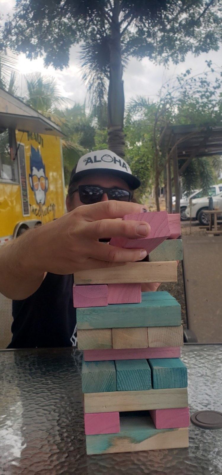 Man with sunglasses and Aloha hat playing Jenga at a food truck in Maui