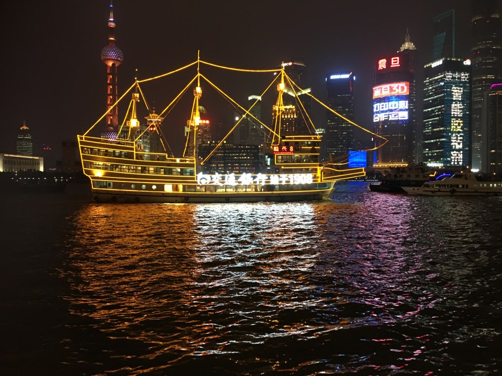 The colours of Shanghai Harbour light up the darkness of the night