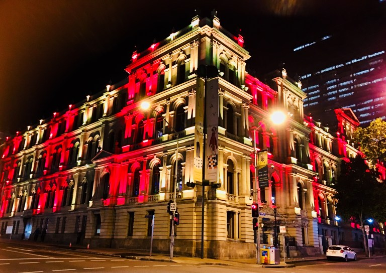 Old brick building, the Treasury Casino Brisbane, with red lights highlighting the sides of the building.
