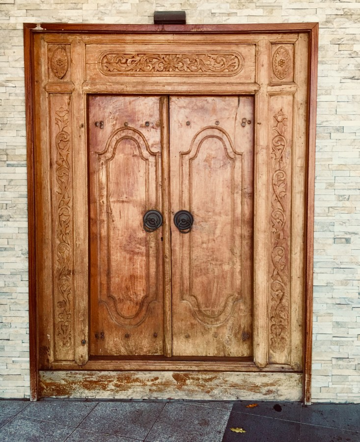 Ornately carved wooden doors set in white brick wall