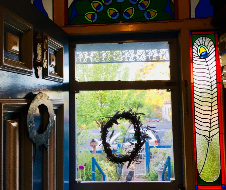 Looking out the front door of Peacock Cottage with a stained glass window on the right side