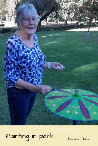 An old woman in a blue print top smiles at the camera over an umbrella. Beautiful park in background