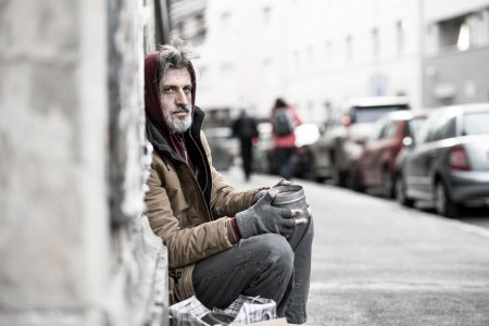 homeless man sitting on street
