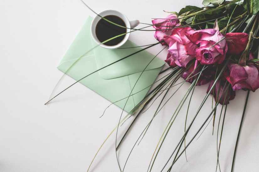 Mediation: Coffee in cup, postcard and roses flowers
