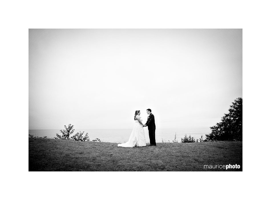A black and white picture of a bride and groom in the rain.