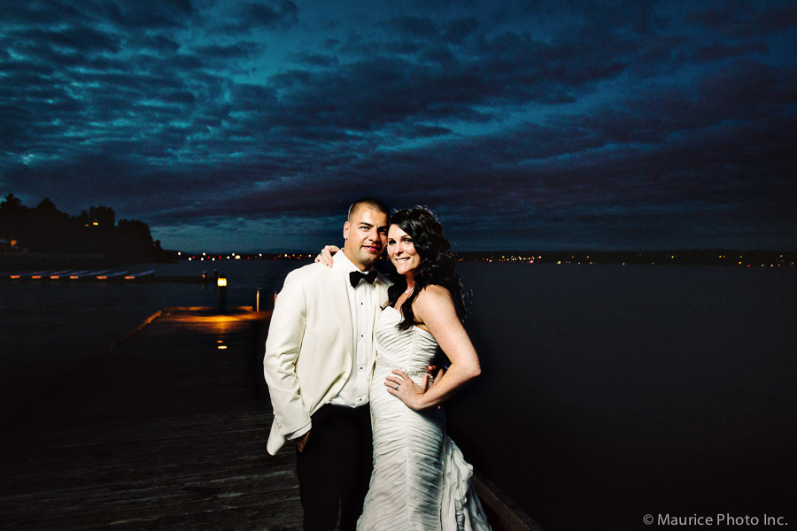 A bride and groom pose for pictures at sunset on the dock at the Seattle Tennis Club