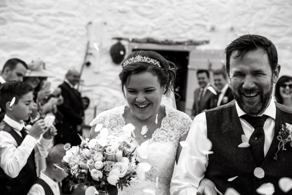 Confetti throw with bride and groom laughing