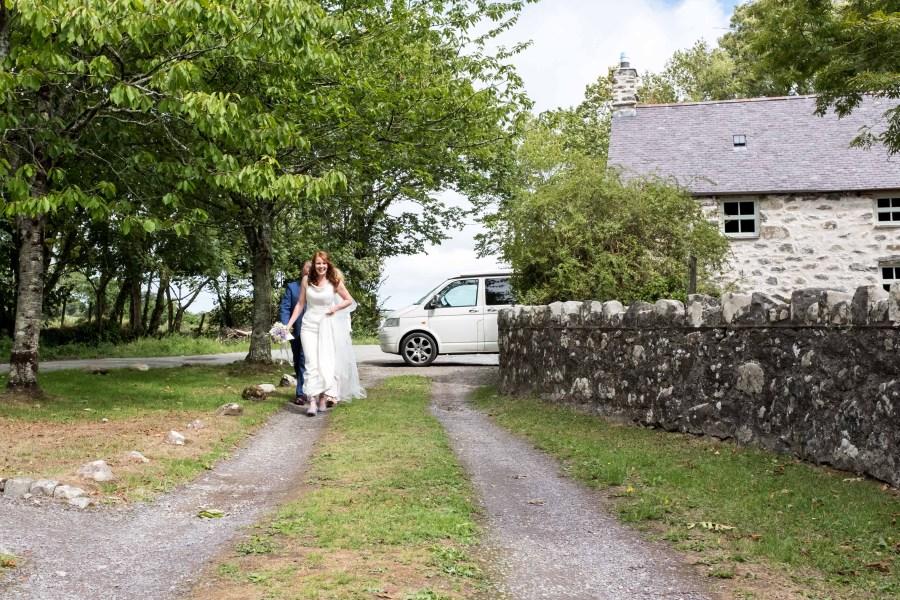Happy bride arriving at Penarth Fawr wedding
