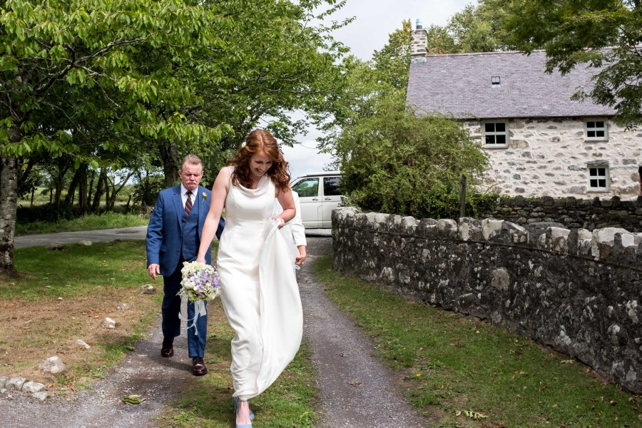 Bride walking closer to Penarth Fawr medieval hall