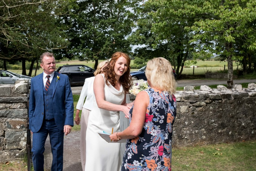 Bride being treated buy the wedding officiant at Penarth Fawr.