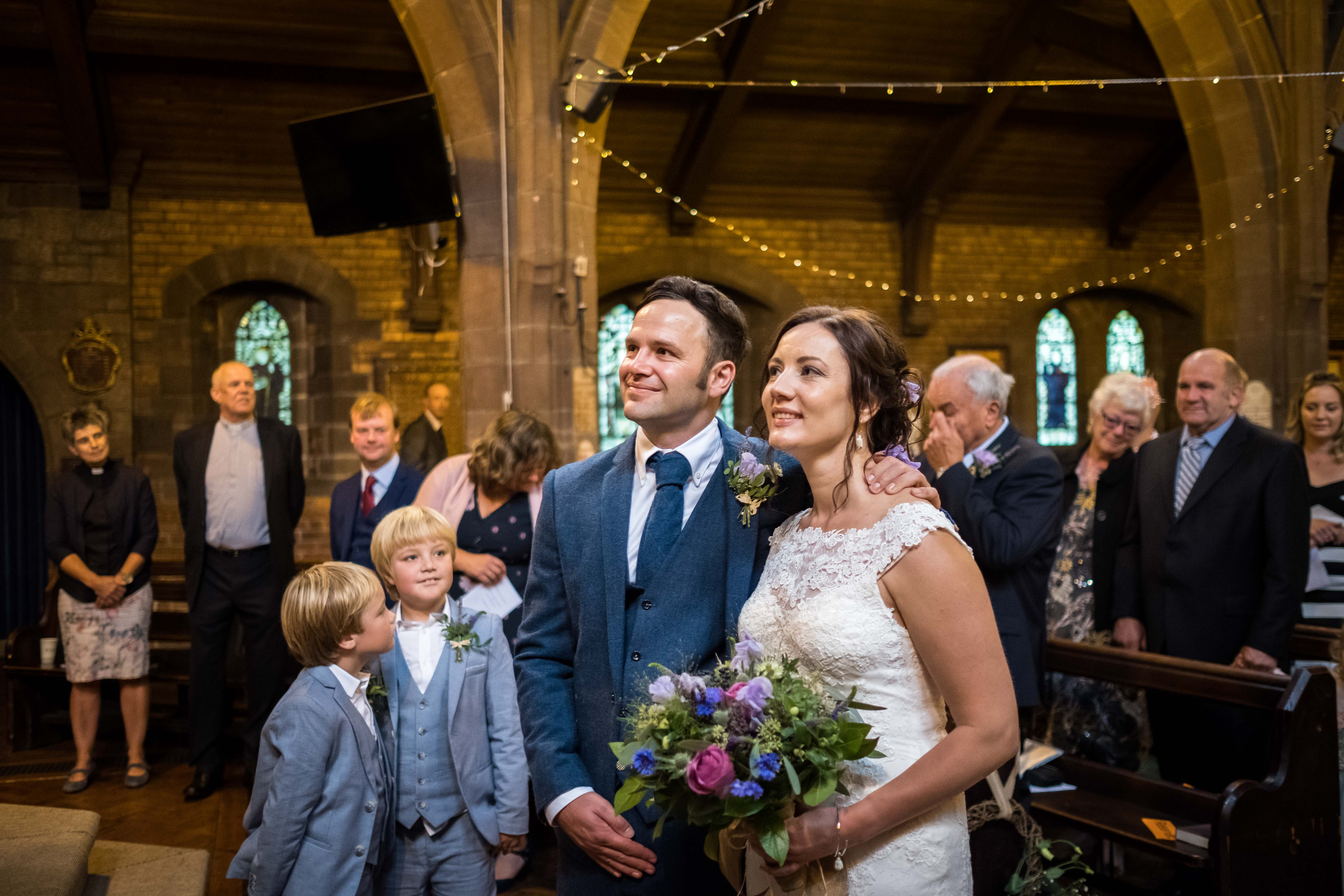 Beautiful image by Chester and North Wales wedding photographer Maurice. The bride and groom are cuddling whilst 2 young paige boys are looking at them and smiling.