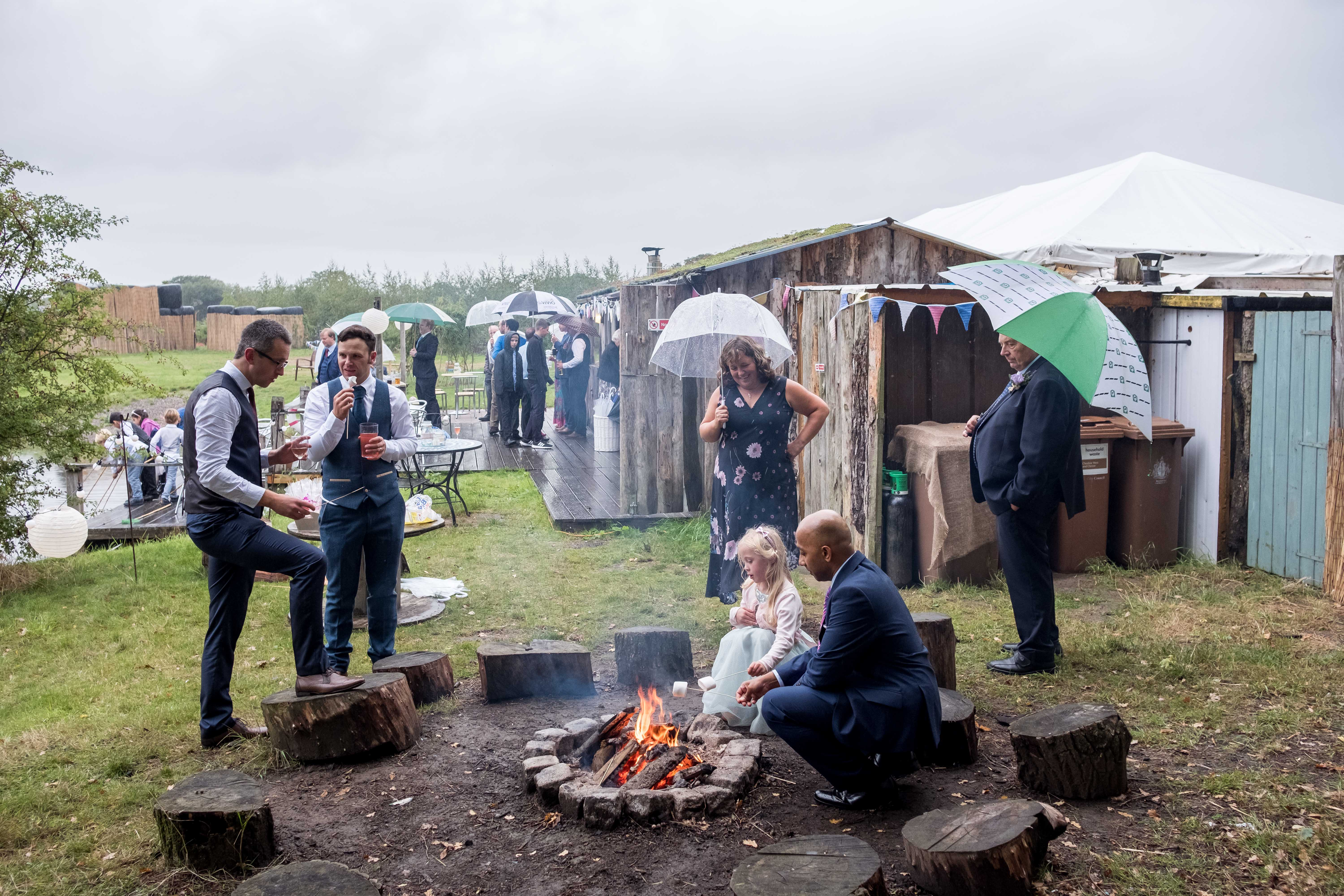 Outside wedding reception in the rain. Guests sitting around the fire toasting marshmallows.