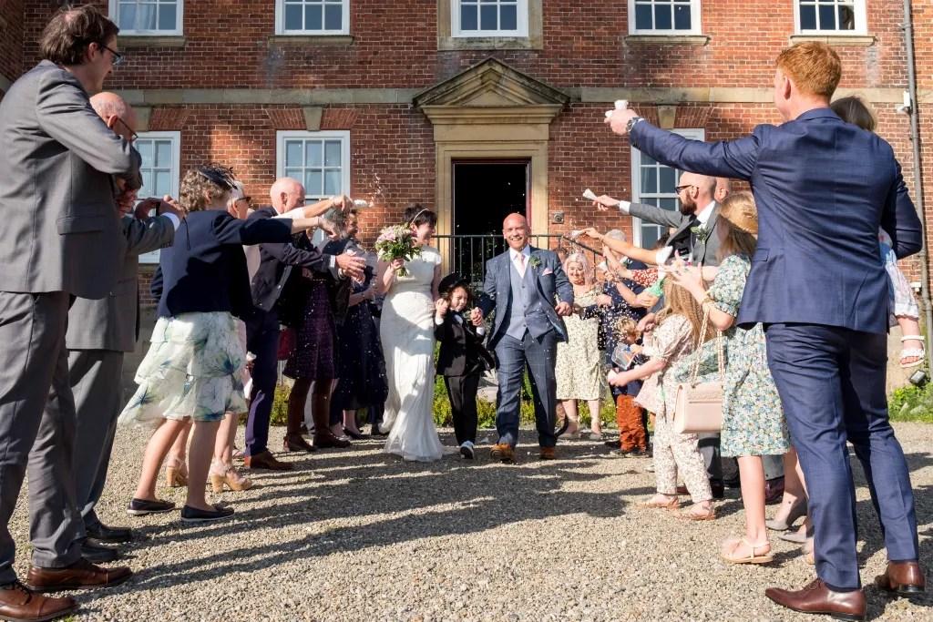 Confetti being thrown everywhere at Trevor Hall wedding Llangollen