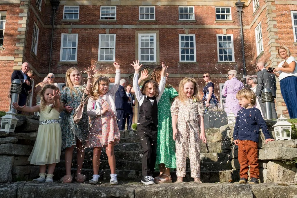 Group of Children throwing confettie outside the front of Trevor Hall Llangollen. After the wedding ceremony of Paul and Rachel