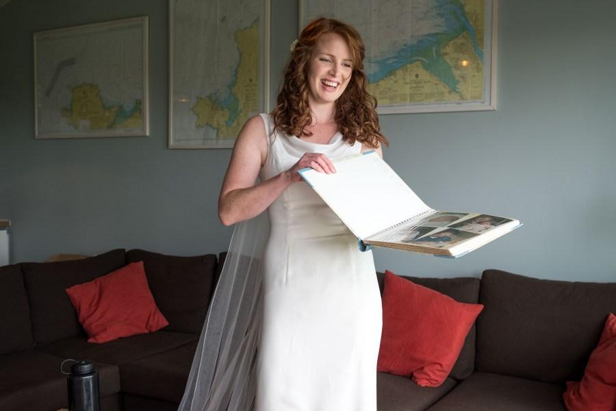 Penarth Fawr wedding ready. Bride in her wedding dress looking through old family photographs.